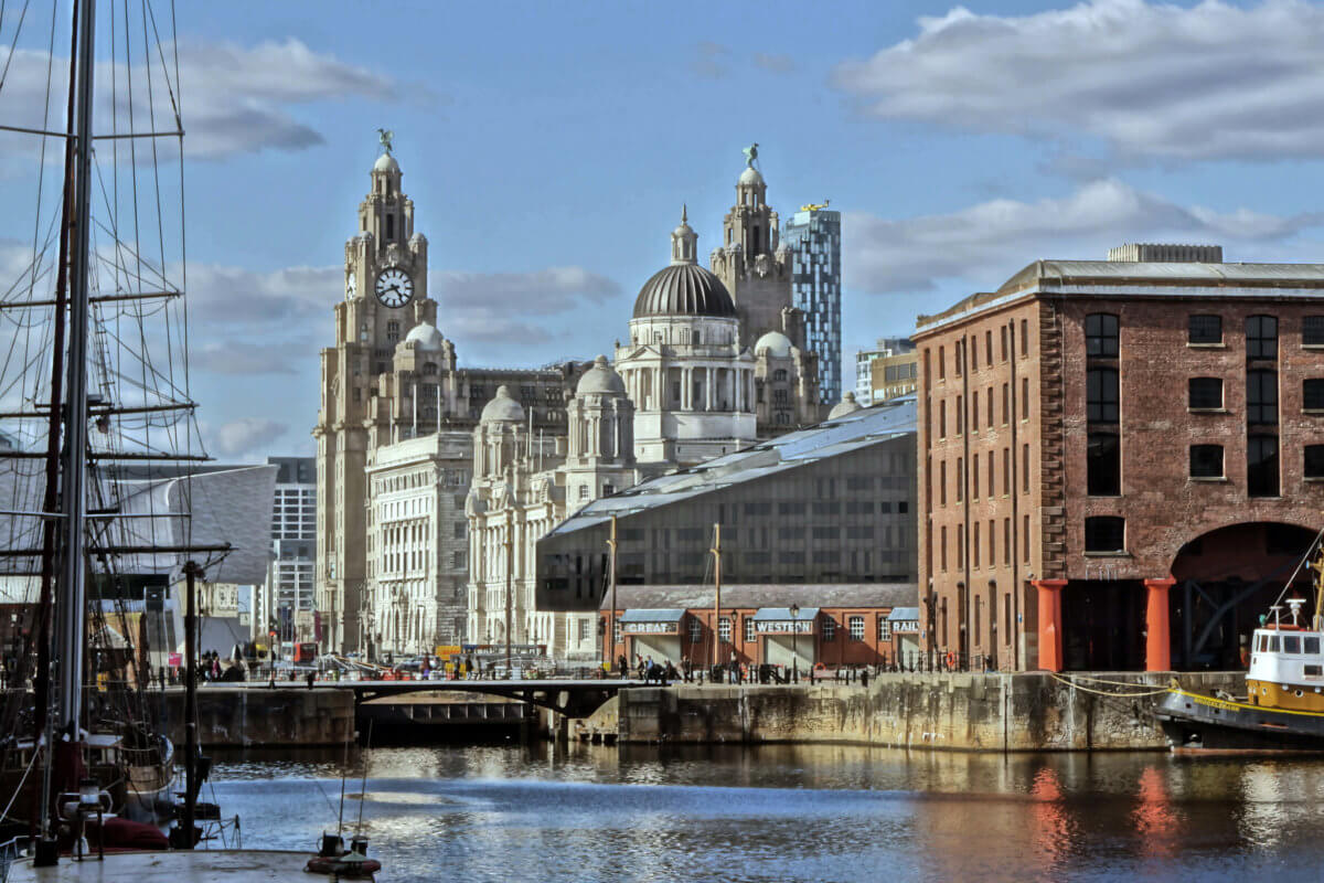 An image of Liverpool city centre. The River Mersey is visible and there are some large buildings in the background. There are also some clouds in the sky and boats on the water.