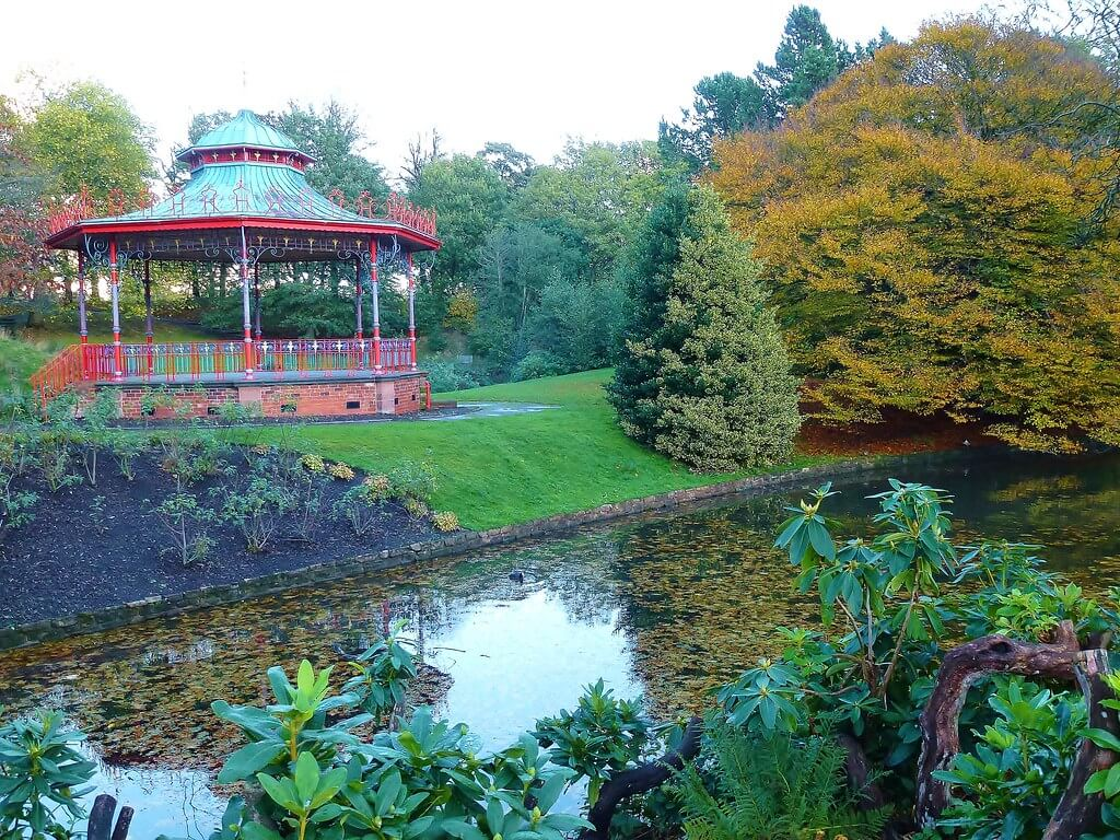 A picture of part of Sefton Park. There is a lake at the front of the image, with different trees visible in the background.