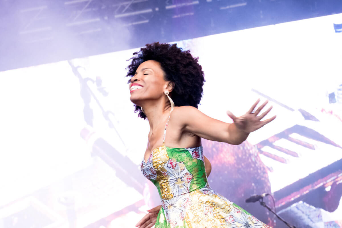 A musician wearing a colourful dress, smiling on stage at the Africa Oyé festival.