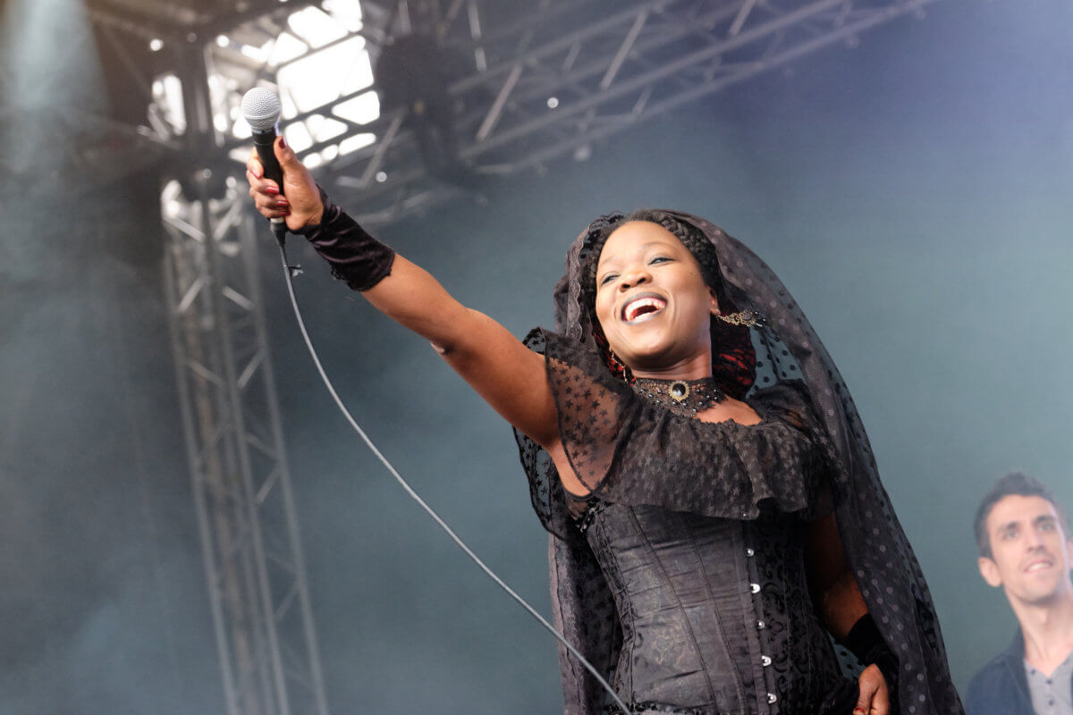 A musician wearing black clothing, smiling and pointing a microphone towards the crowd on stage at the Africa Oyé festival.