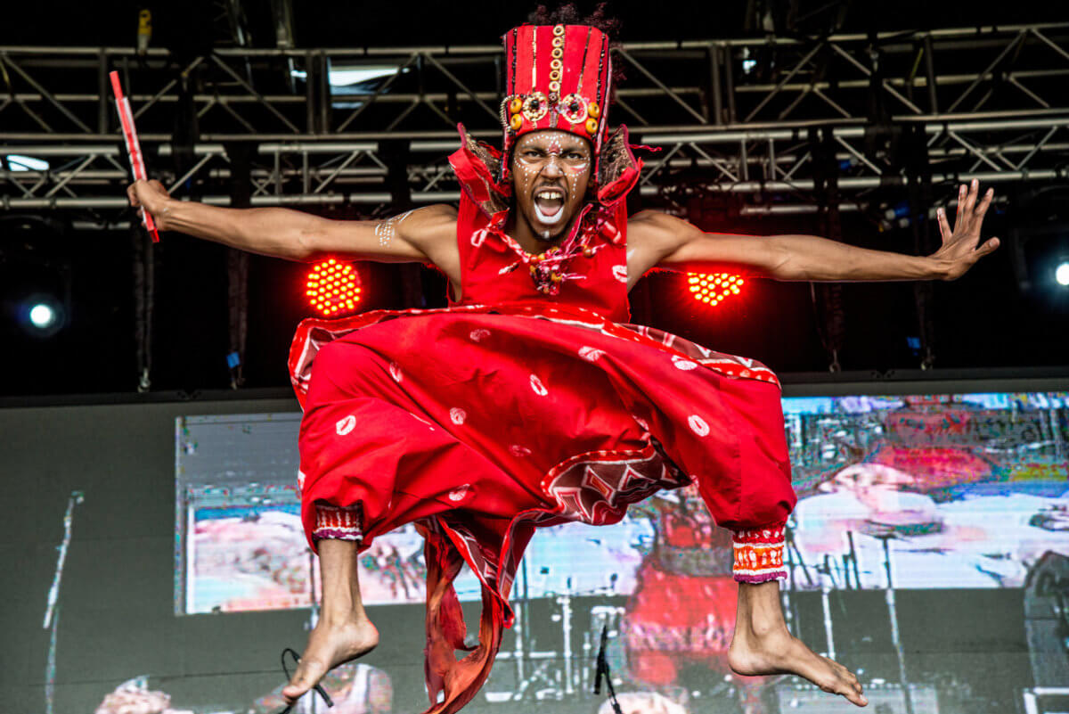 A performer wearing red clothing, on stage at the Africa Oyé festival. They are in mid-air, with their arms pointing away from them and knees towards their chest.