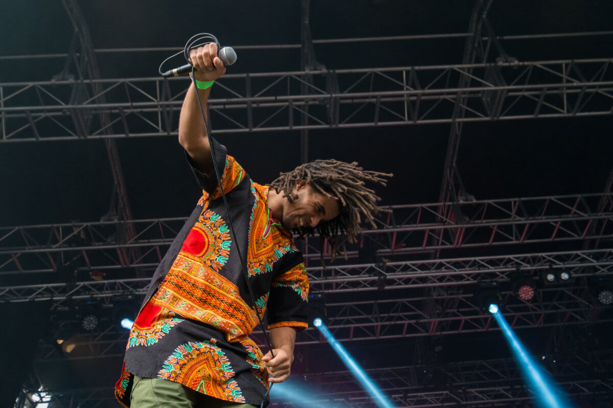A musician on the Africa Oyé stage, looking towards the ground and holding a microphone towards the crowd at Sefton Park.