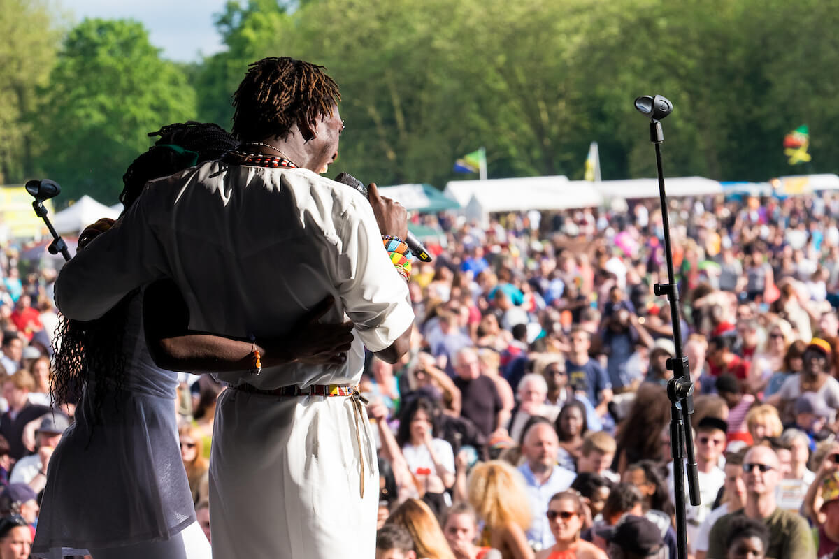 Two musicians wearing white clothing, with their back towards the camera and arms around each other. There is a packed crowd in front of them at the Africa Oyé festival.