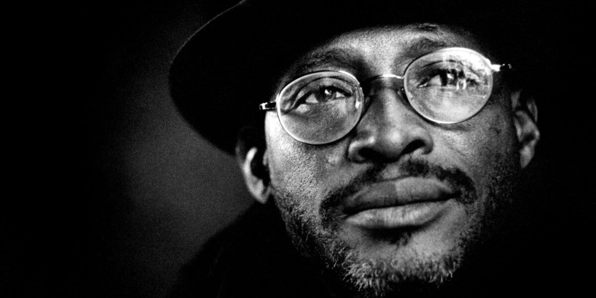 A black and white, close-up image of a musician, wearing glasses and a hat.