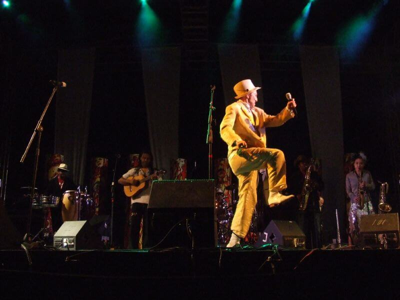 Image of SKA CUBANO on stage. One member is in front of the others, wearing a yellow suit and hat and holding a microphone. The other members are each playing an instrument.
