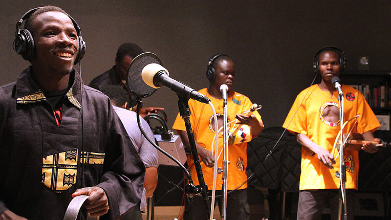 Image of group KENGE KENGE. They are wearing headphones, with microphones placed in front of them.