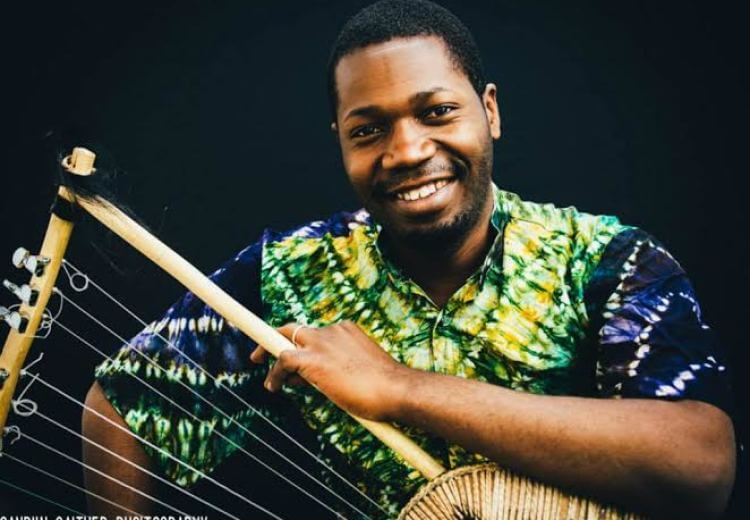 Image of KINOBE HERBERT, smiling and holding a stringed instrument.