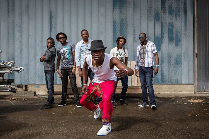 Image of band Mokoomba. One member of the band stands in front of the other five members.